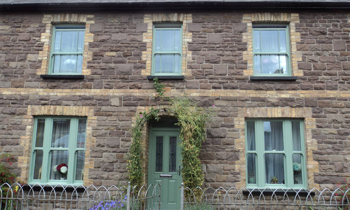 Chartwell green uPVC sliding sash windows and entrance door